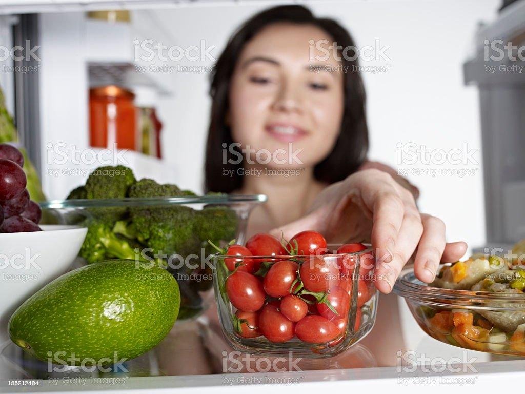 Woman Taking Cherry Tomato royalty-free stock photo