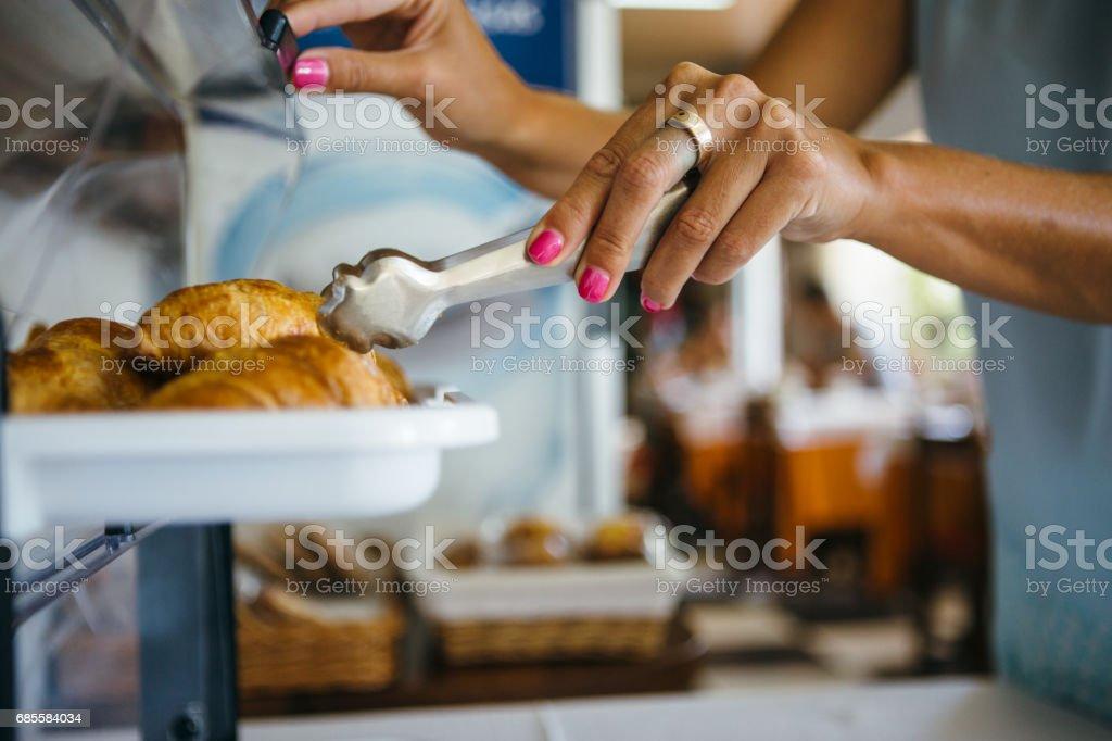 Woman taking croissant stock photo
