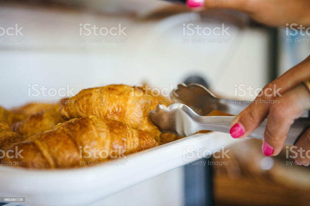 Woman taking croissant with tongs stock photo