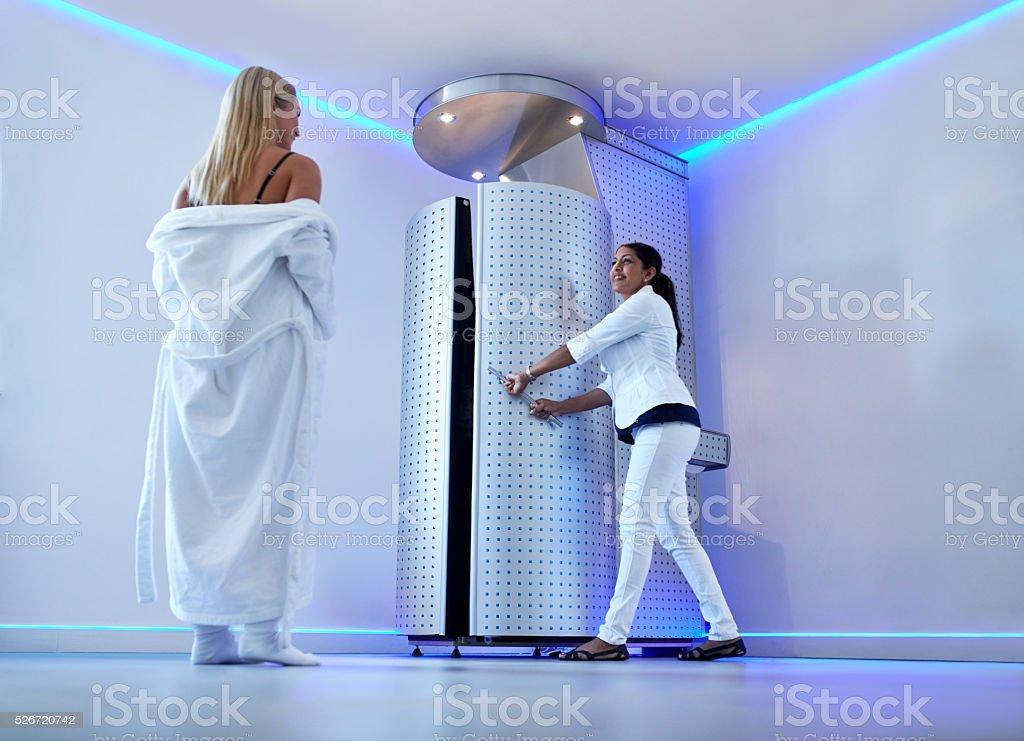 Woman taking cryosauna treatment at cosmetology clinic stock photo