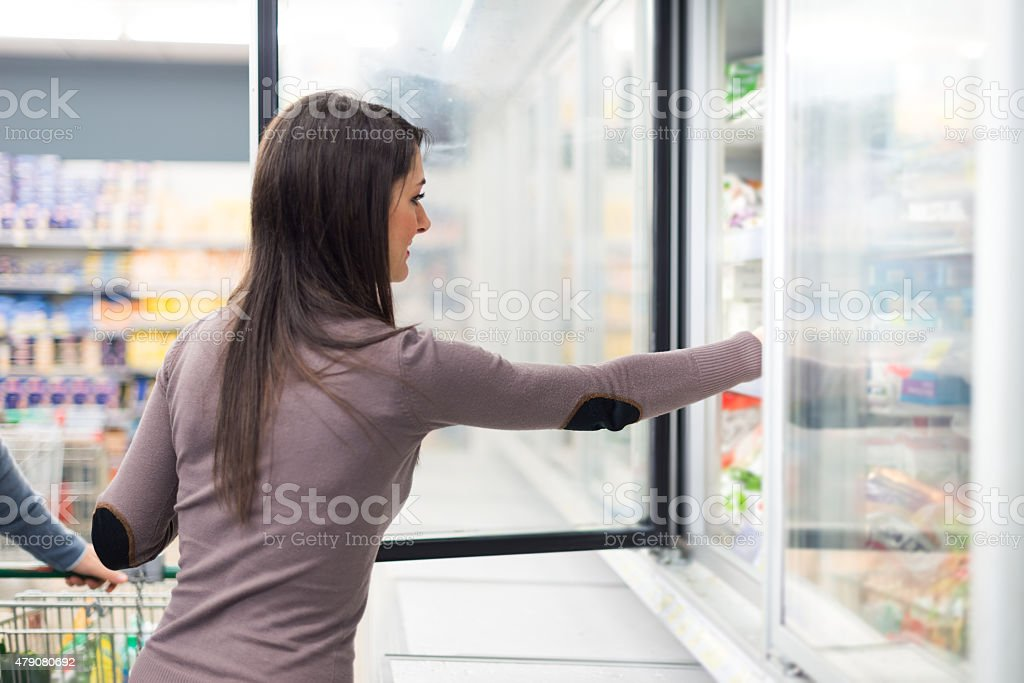 Woman taking deep frozen food from a freezer stock photo