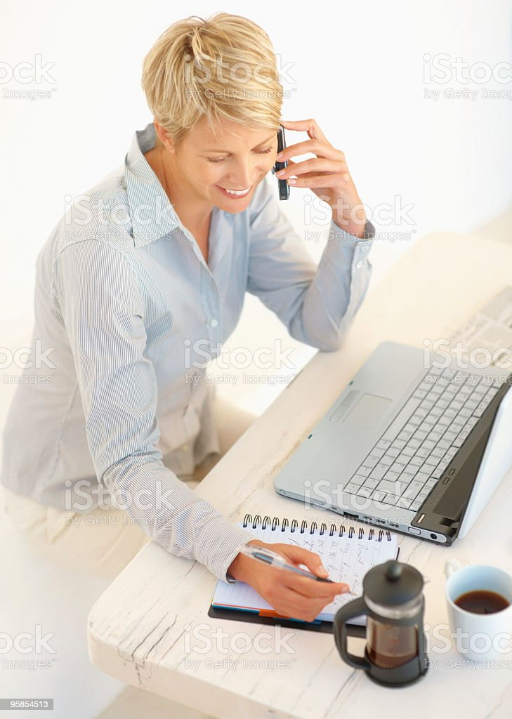 Woman taking down a message speaking on the phone royalty-free stock photo