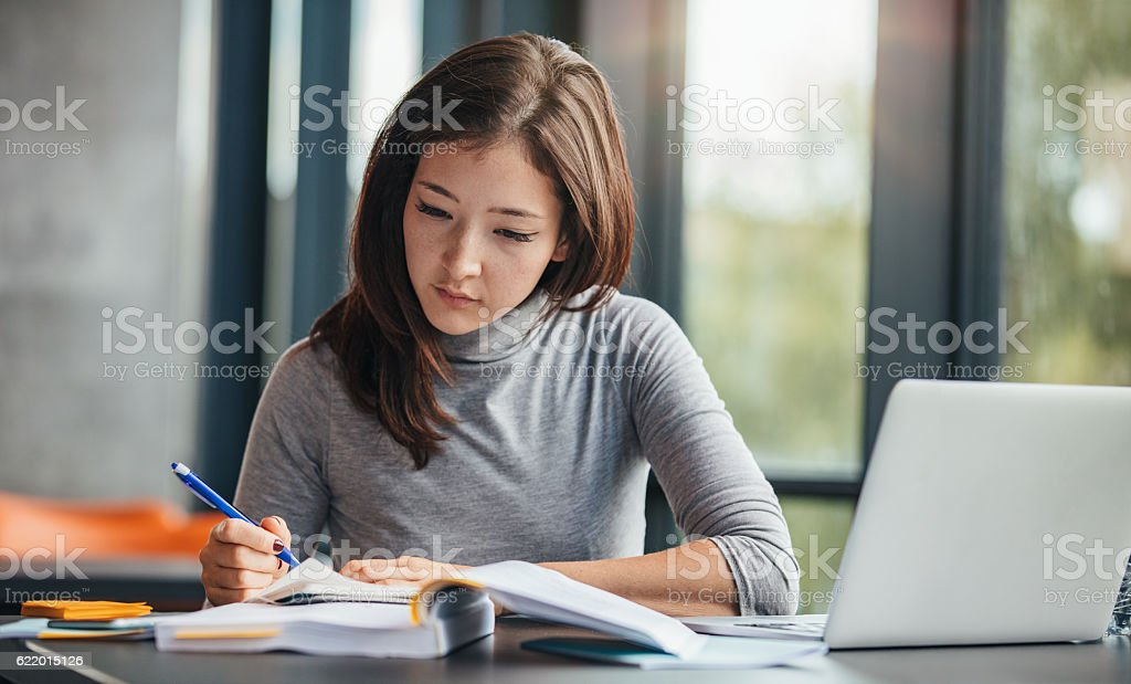 Woman taking down notes in diary stock photo