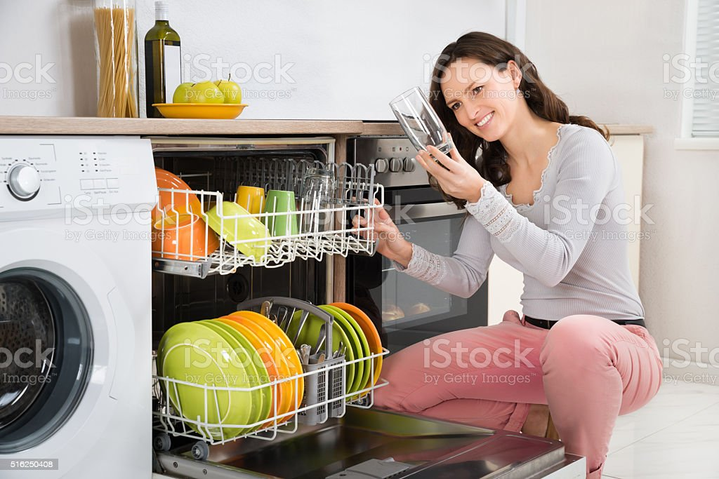 Woman Taking Drinking Glass From Dishwasher stock photo