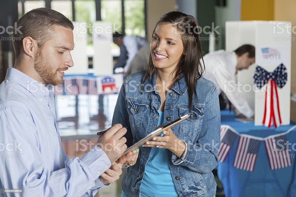Woman taking exit poll interview on election day stock photo