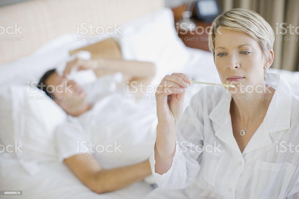 Woman taking husband temperature royalty-free stock photo