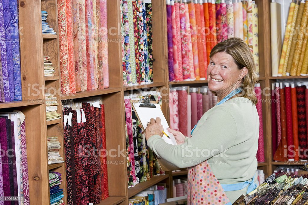 Woman taking inventory in fabric shop stock photo