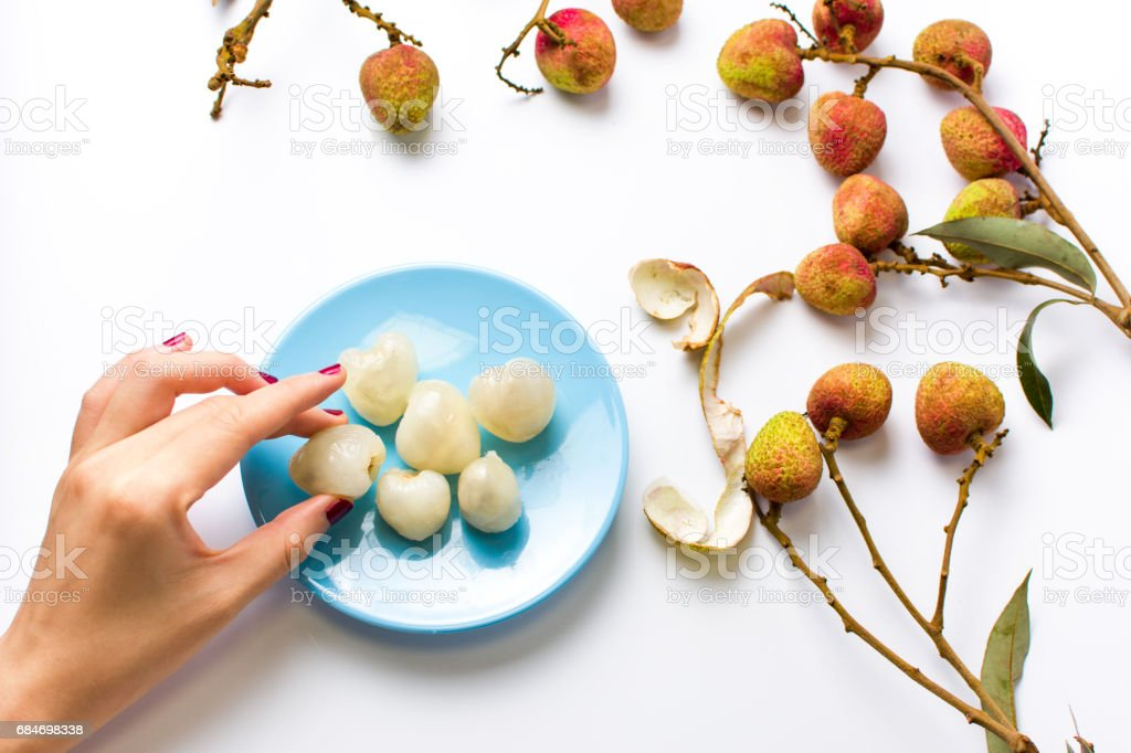 Woman taking lychee tropical fruit from a plate stock photo