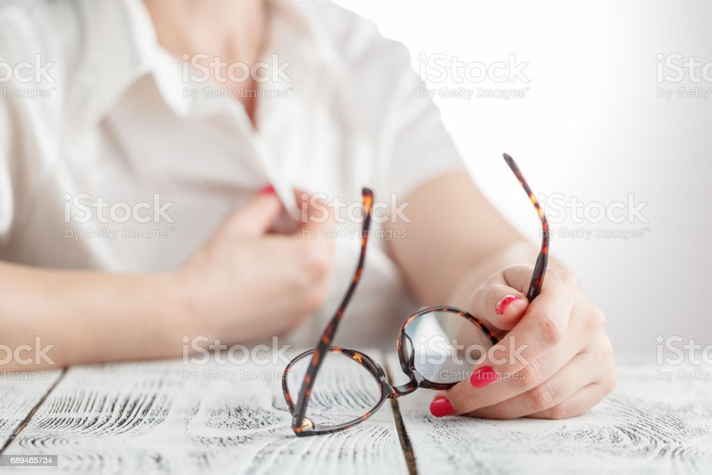 woman taking off her glasses stock photo