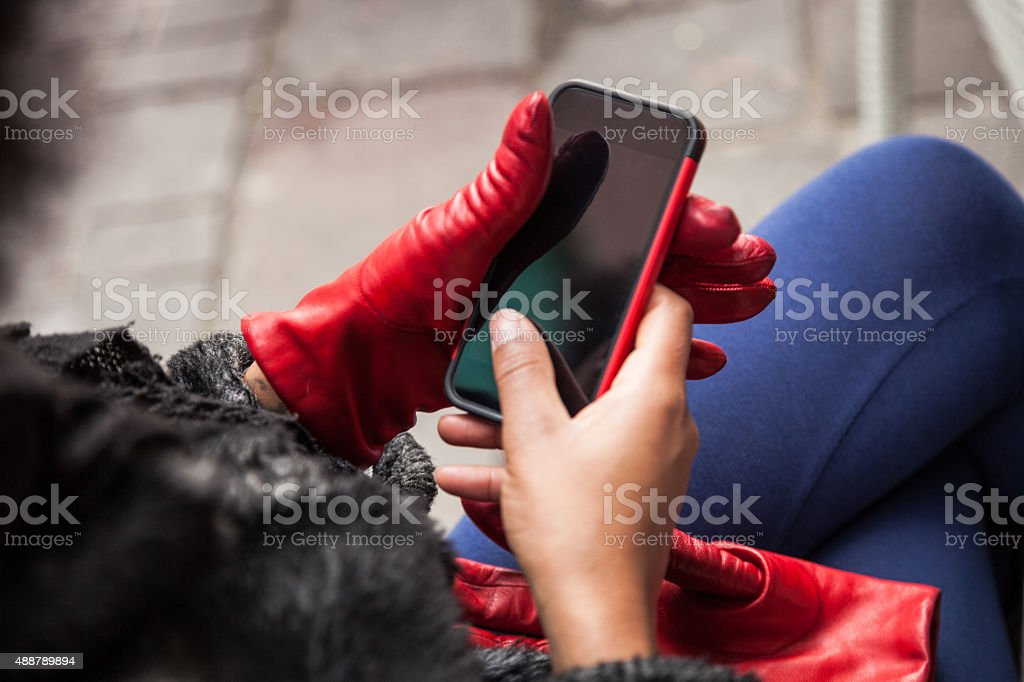 Woman taking off the gloves to write on the phone stock photo