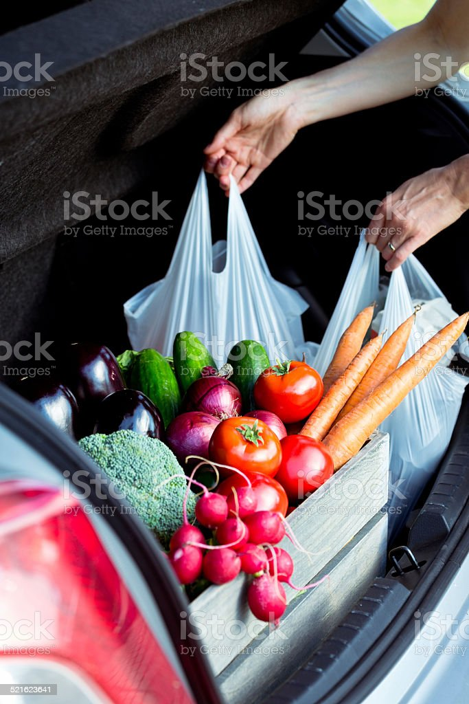 Woman taking out shopping bags from car trunk stock photo