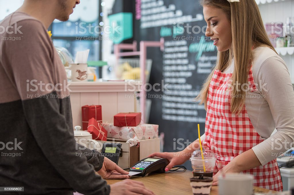Woman taking payment from customer in cake shop counter stock photo
