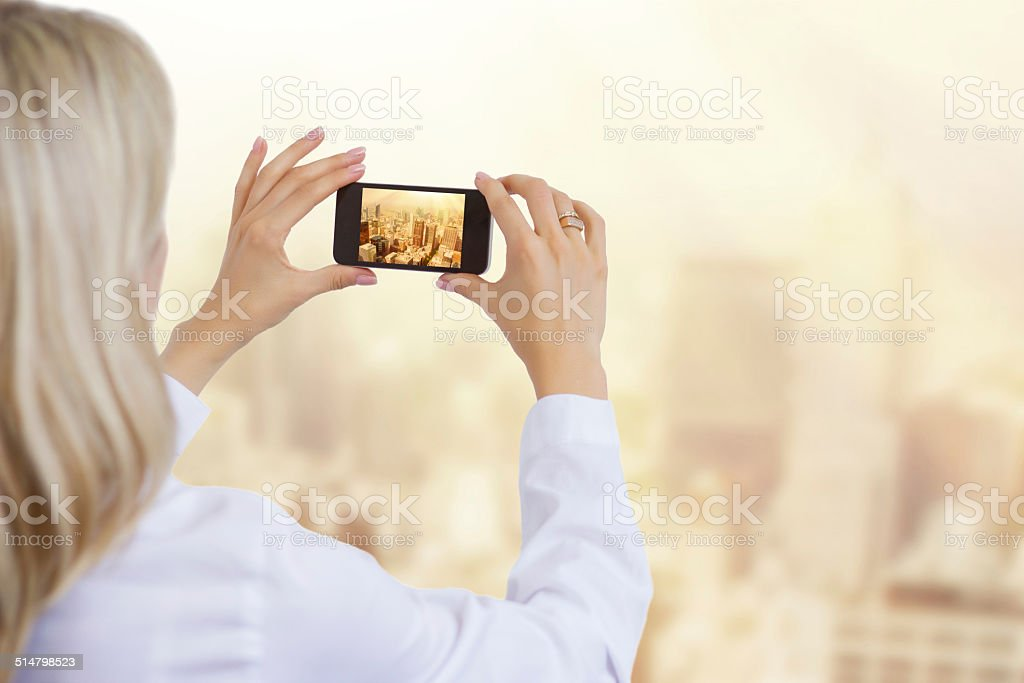Woman taking photo of city in morning light stock photo