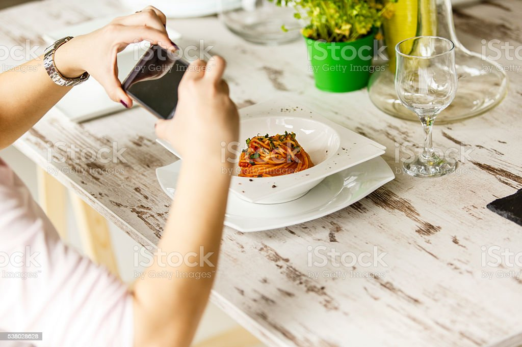 Woman taking photo of food with smartphone stock photo