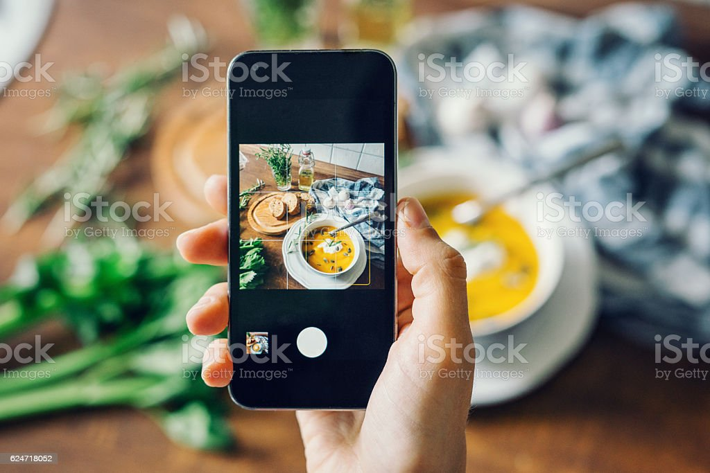 Woman taking photo of pumpkin soup with smartphone stock photo