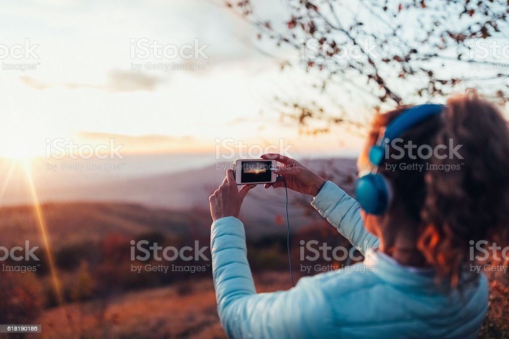 Woman taking photo of the sunset stock photo