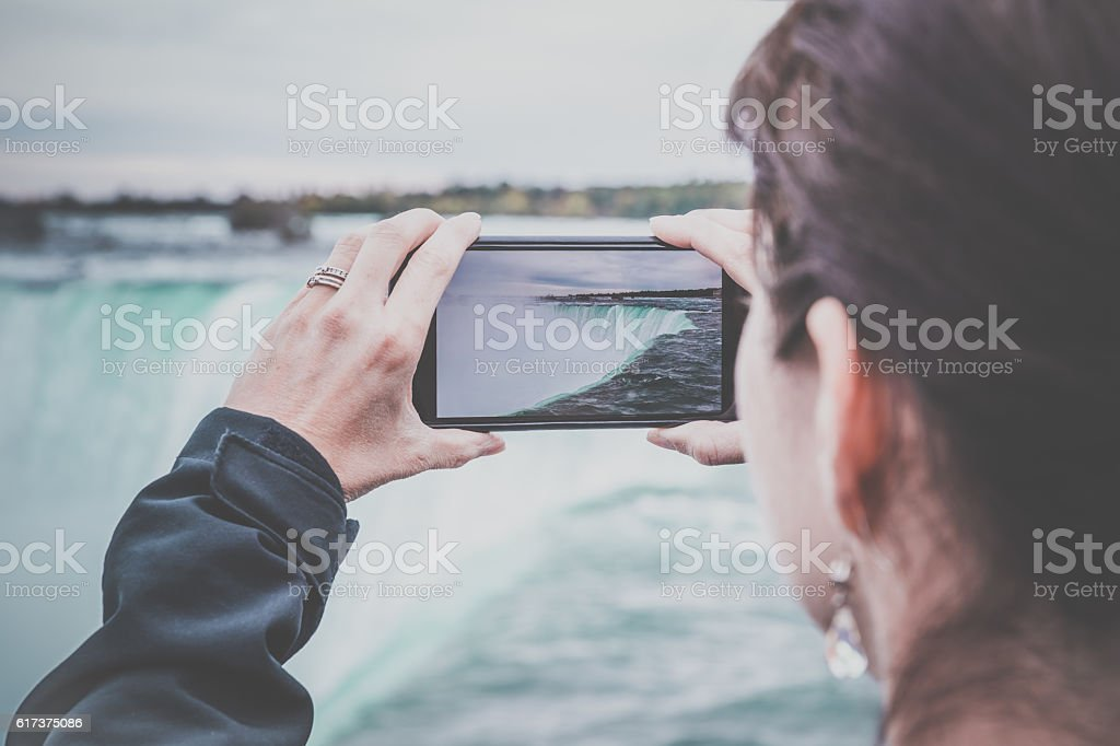 Woman Taking Picture at Niagara Falls with Smart phone stock photo