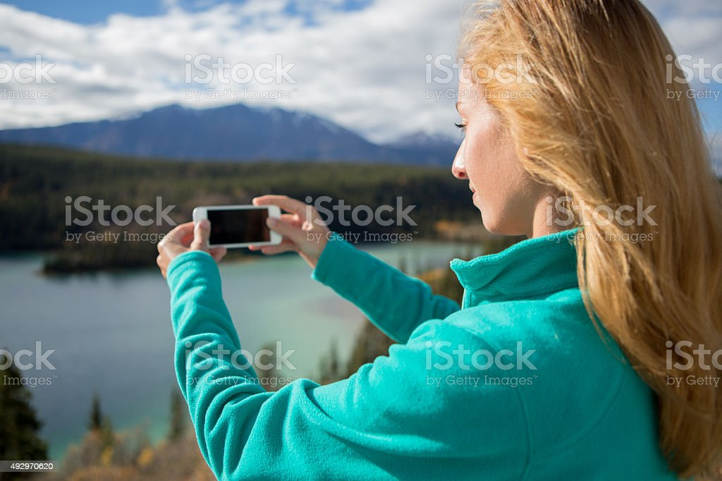 Woman taking picture of mountain lake landscape using mobile phone stock photo