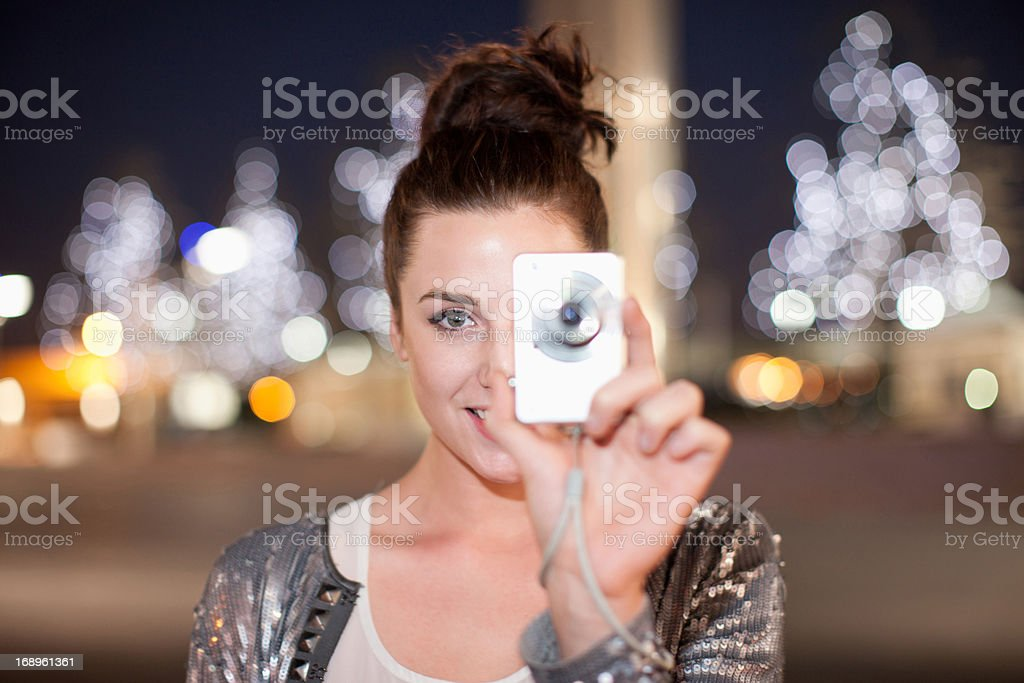 Woman taking picture on city street at night stock photo
