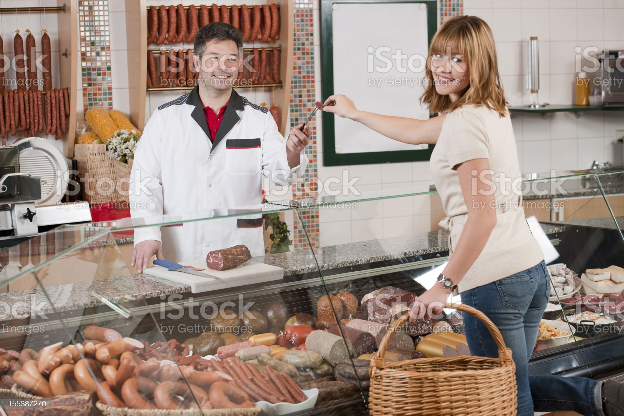 Woman taking piece of sausage in butchers shop royalty-free stock photo