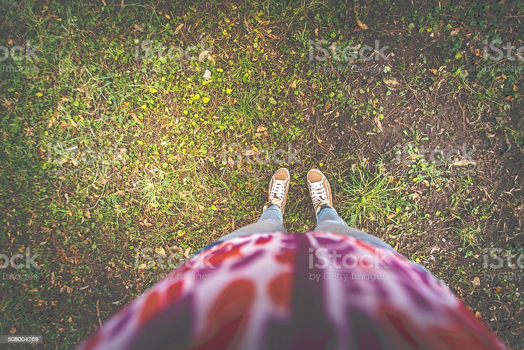Woman taking selfie of her legs on grass stock photo