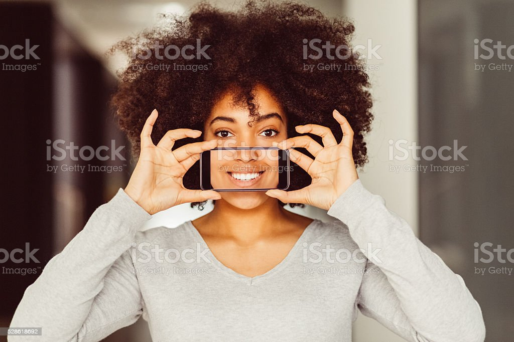 Woman taking selfie of toothy smile stock photo