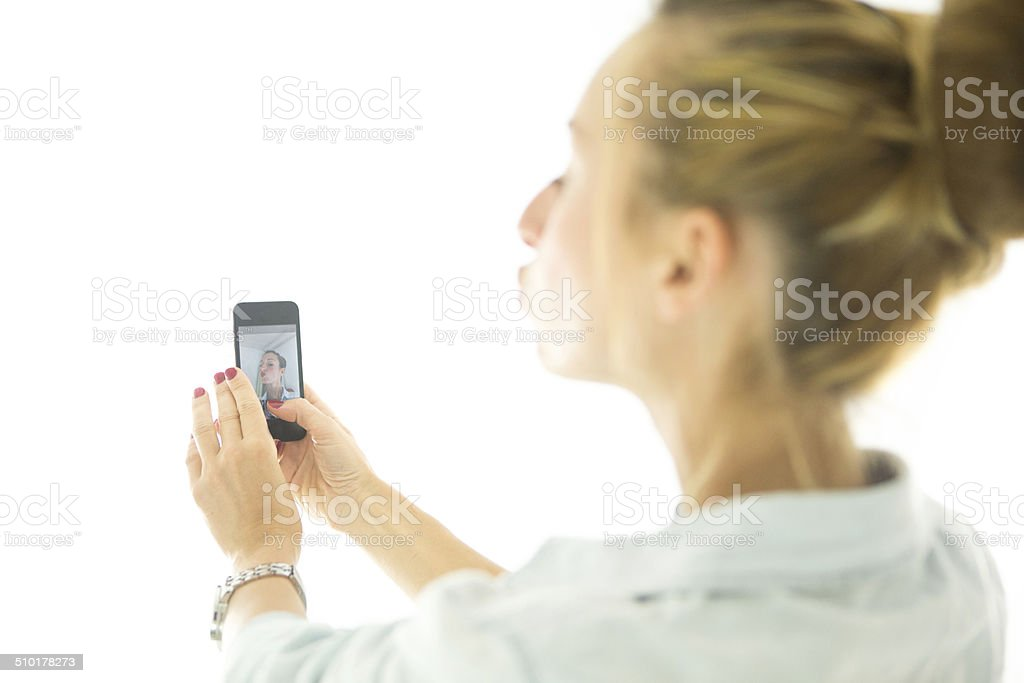 Woman taking selfie with smartphone stock photo