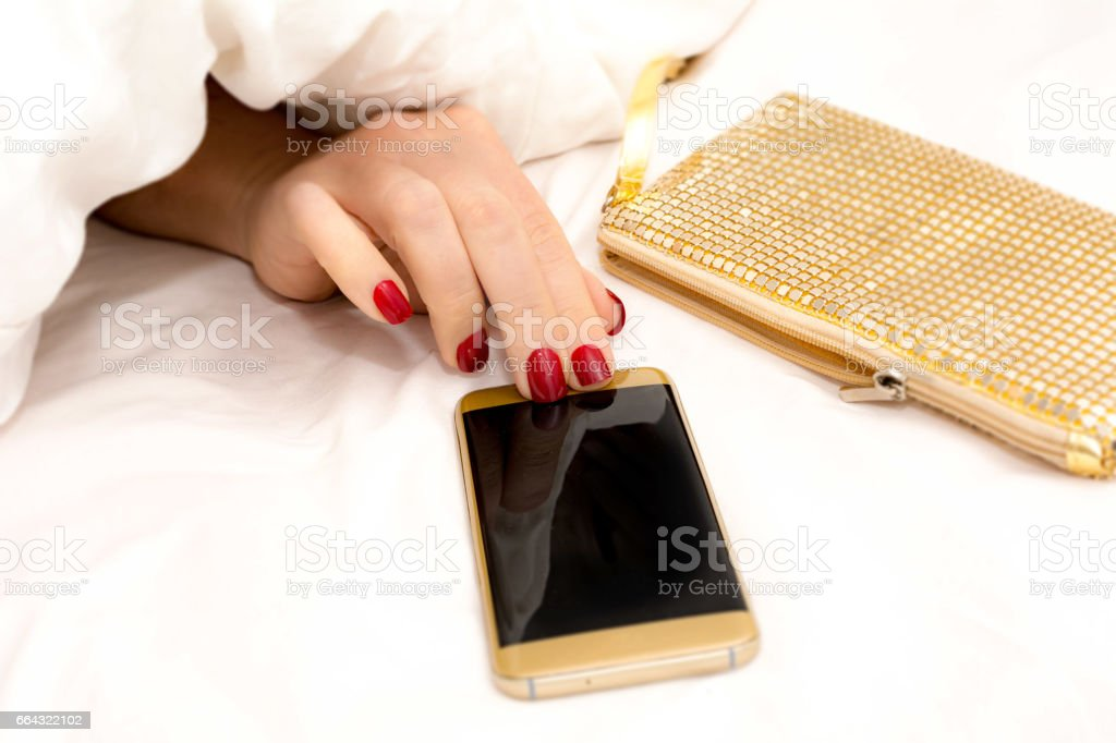 Woman taking Smart phone from under her white duvet from gold sequin clutch stock photo