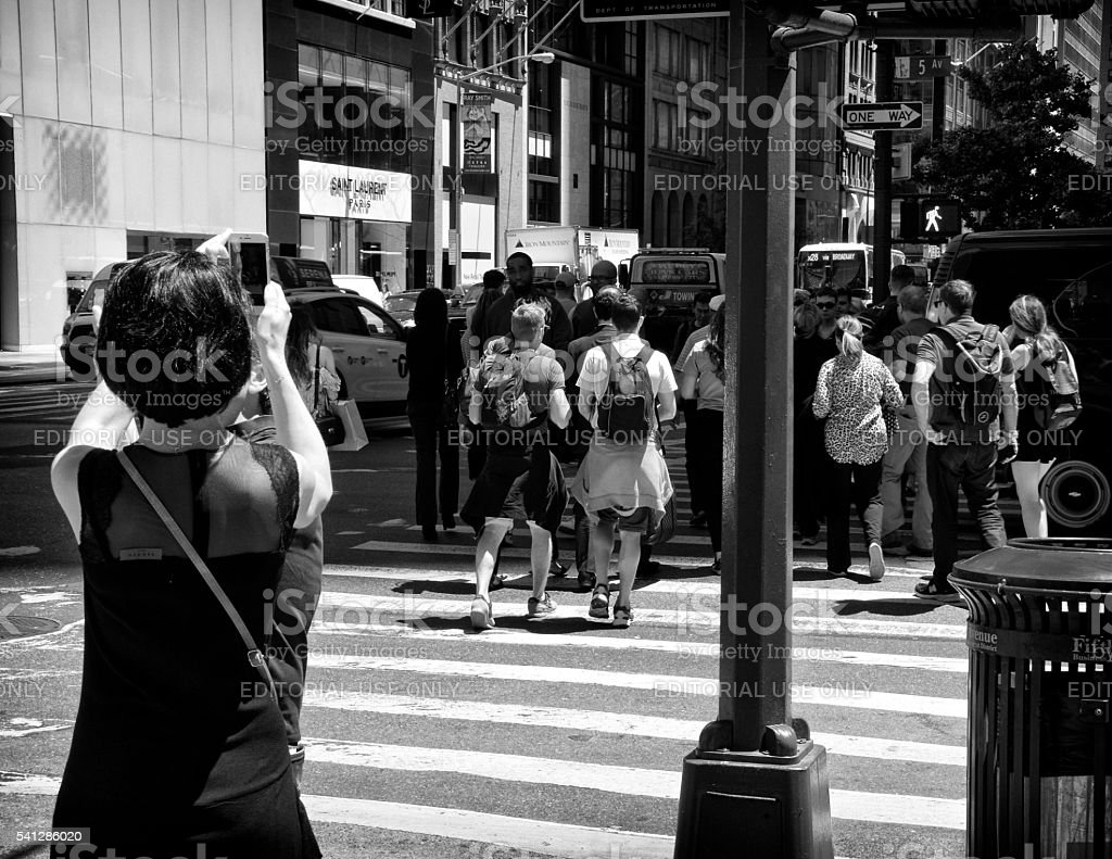 Woman taking smartphone photos, 5th Ave, Midtown Manhattan, NYC stock photo