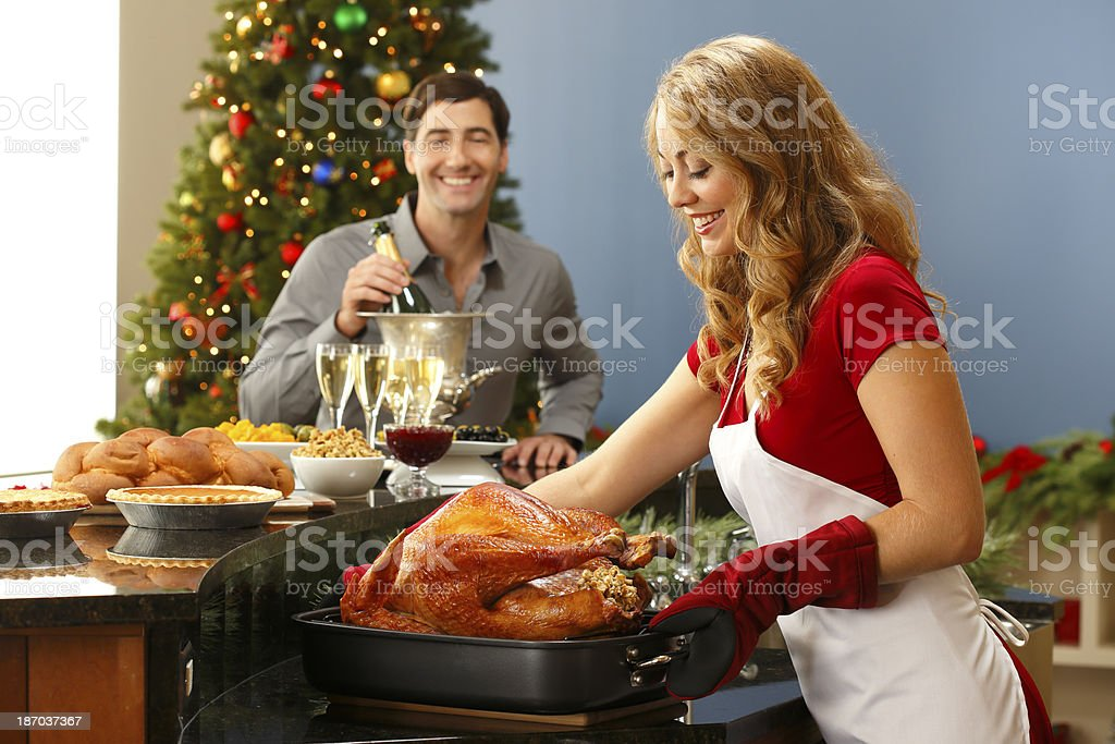 Woman Taking Turkey Out Of The Oven For Christmas Dinner royalty-free stock photo