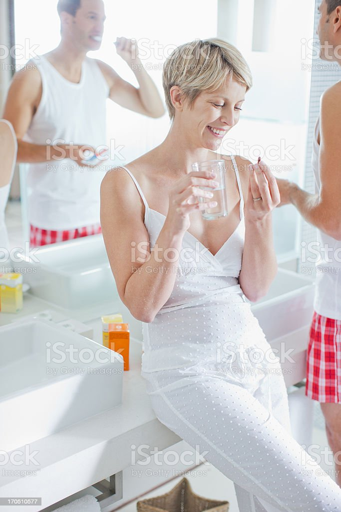 Woman taking vitamins in the morning royalty-free stock photo