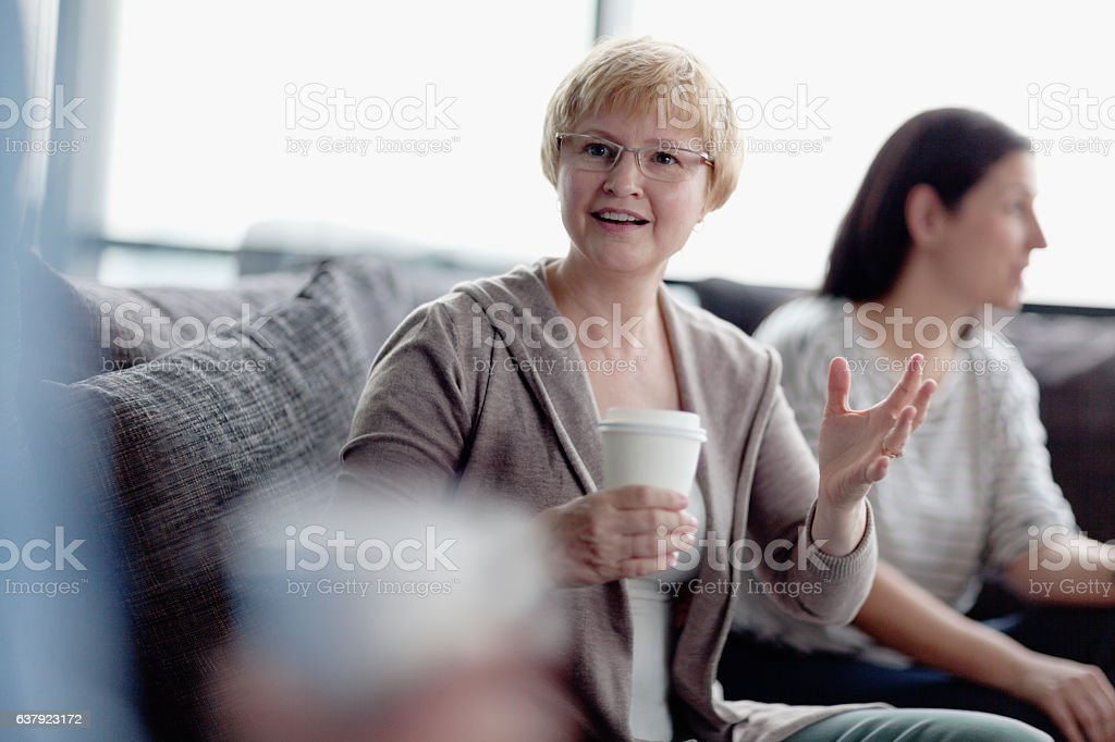 Woman talking during coffee break with colleagues stock photo