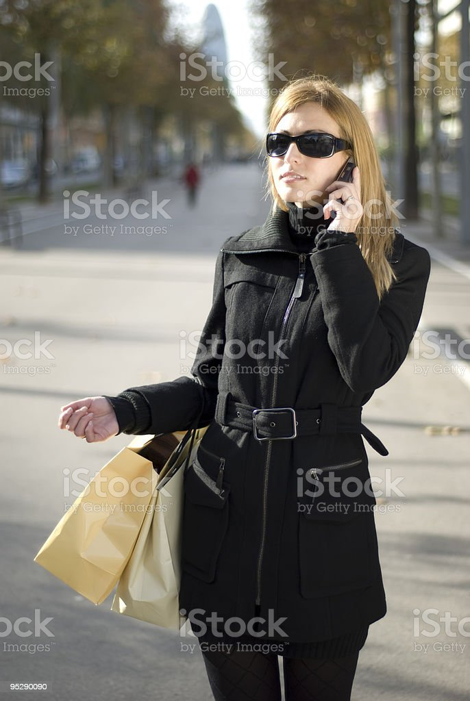 Woman talking on a mobile holding bags royalty-free stock photo