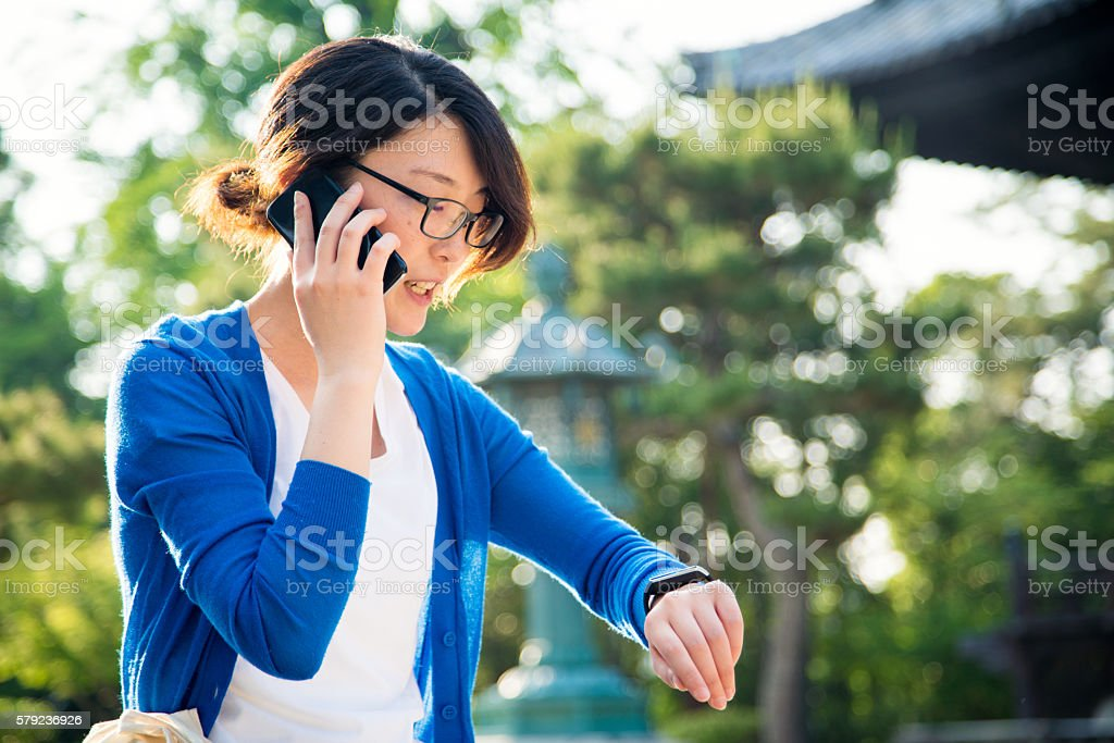 Woman talking on a smartphone at a Japanese Temple stock photo