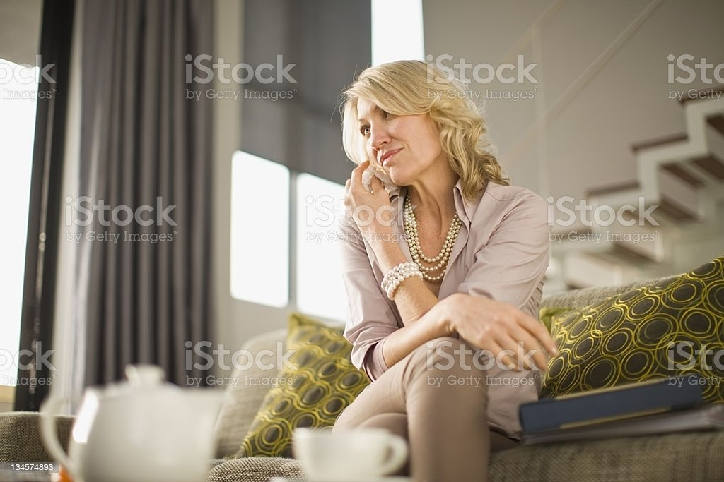 Woman talking on cell phone on couch stock photo
