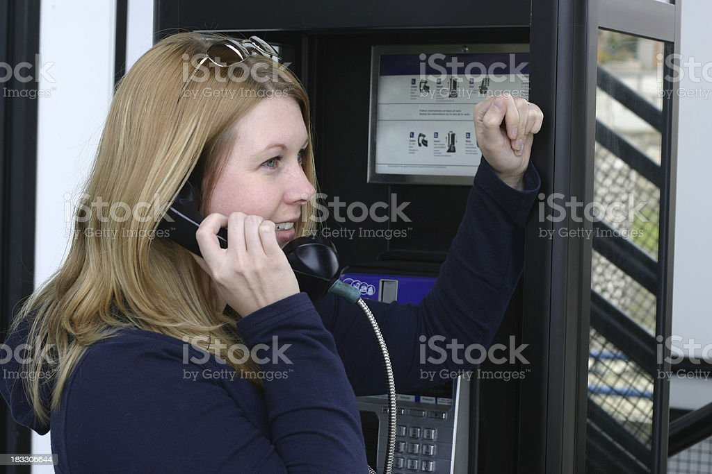 Woman talking on pay phone royalty-free stock photo
