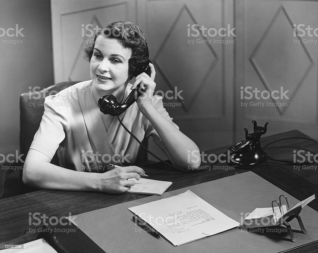 Woman talking on phone at desk (B&W) stock photo
