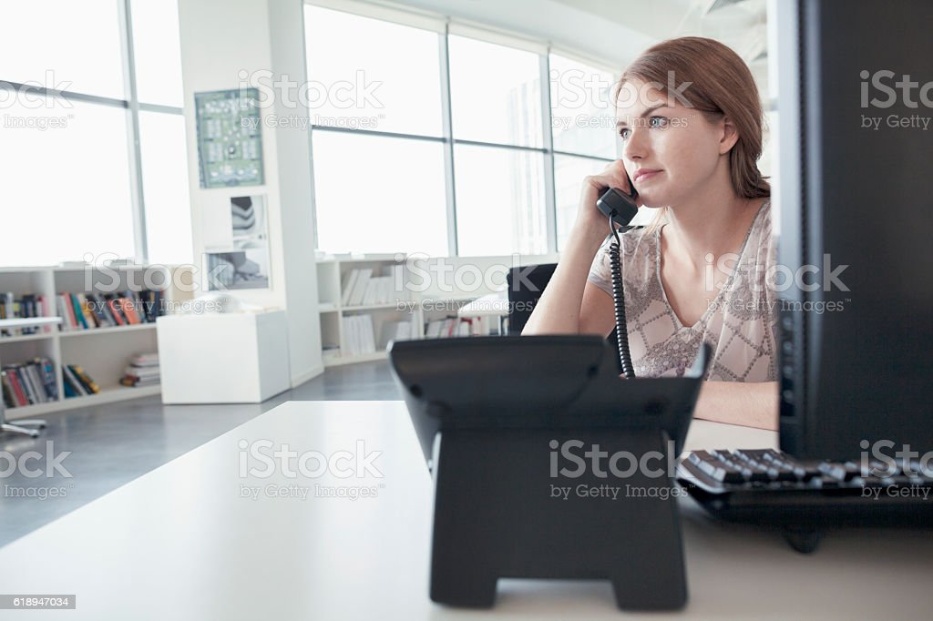 Woman talking on phone in business office stock photo