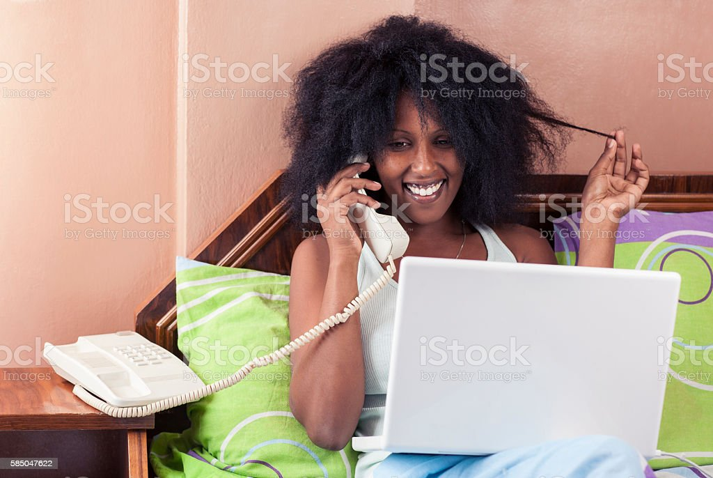 Woman talking on phone while resting in bed with notebook. stock photo
