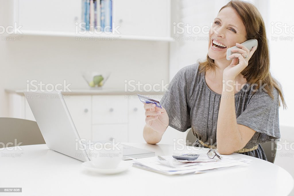 Woman talking on telephone and holding credit card stock photo