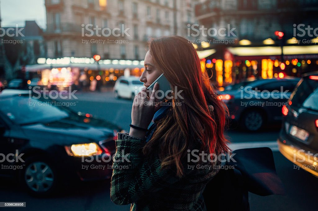 Woman talking on the phone at night stock photo