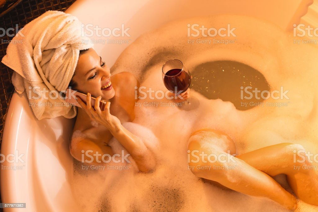Woman talking on the phone while enjoying in bubble bath. stock photo