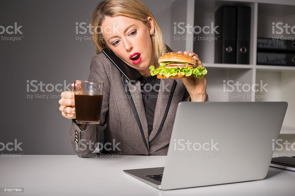 Woman talking on the phone while having burger and coffee stock photo
