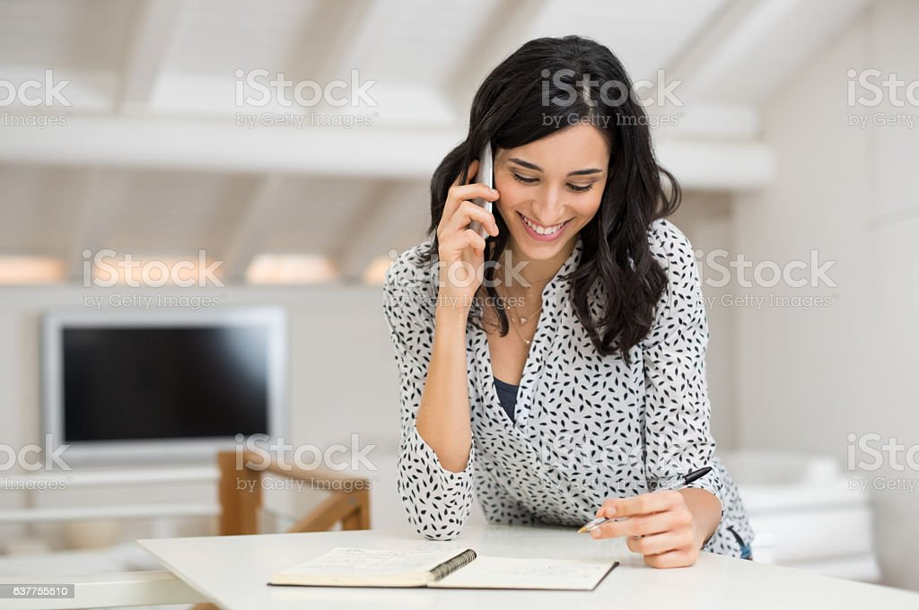 Woman talking over phone at home stock photo