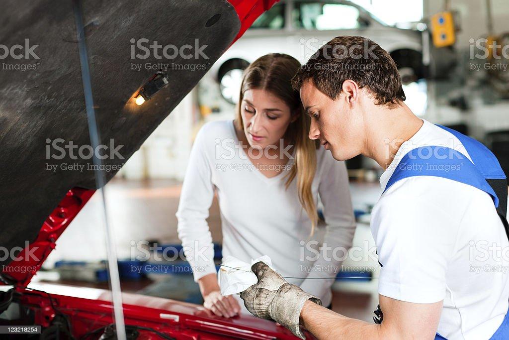 Woman talking to car mechanic in repair shop stock photo