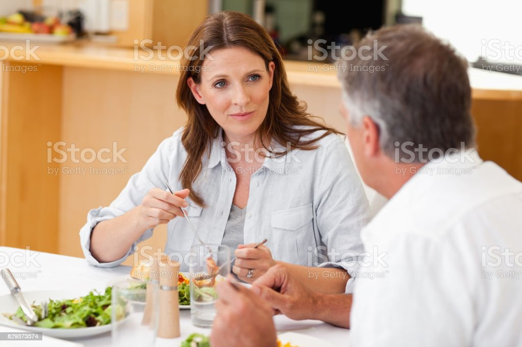 Woman talking to husband during dinner stock photo
