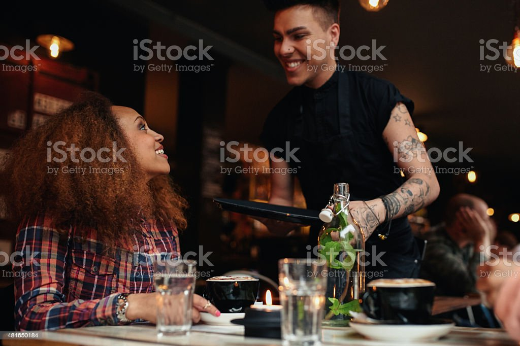 Woman talking to waiter at cafe stock photo