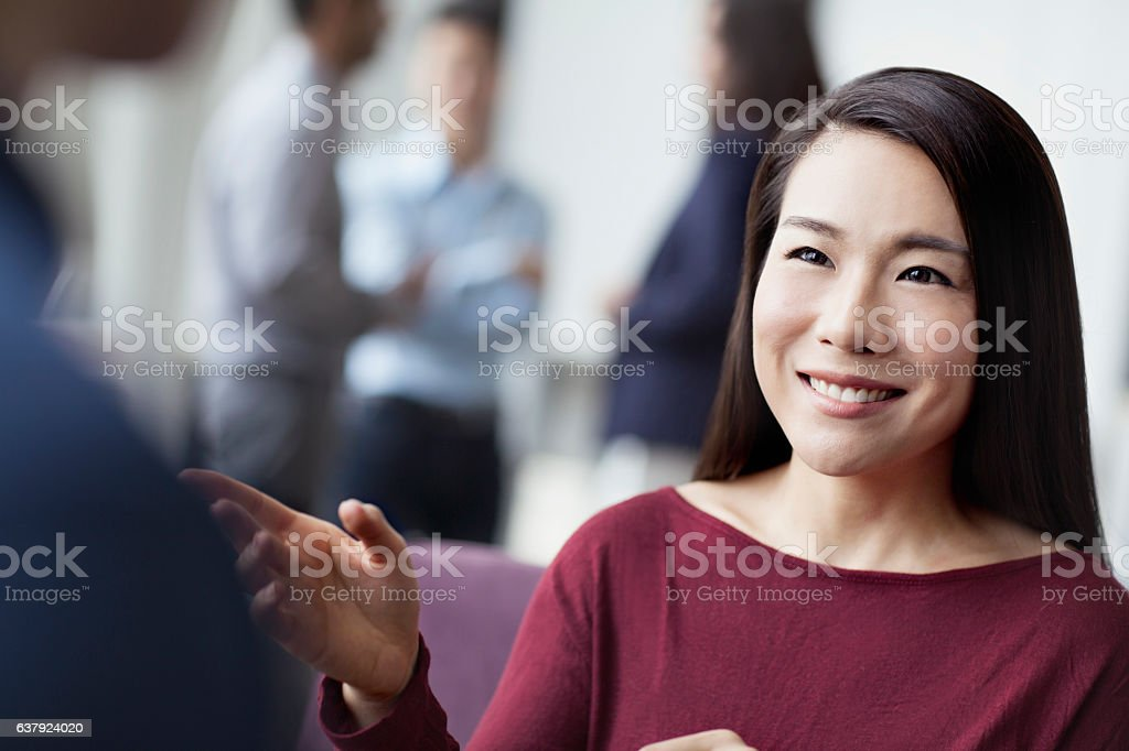 Woman talking with colleagues in office stock photo