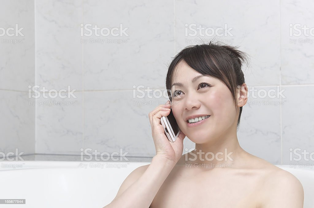 Woman talking with smart phone in bathroom royalty-free stock photo