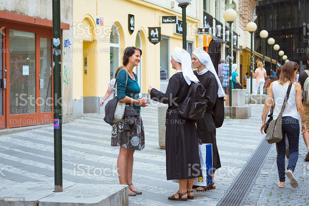 Woman talking with two nuns stock photo